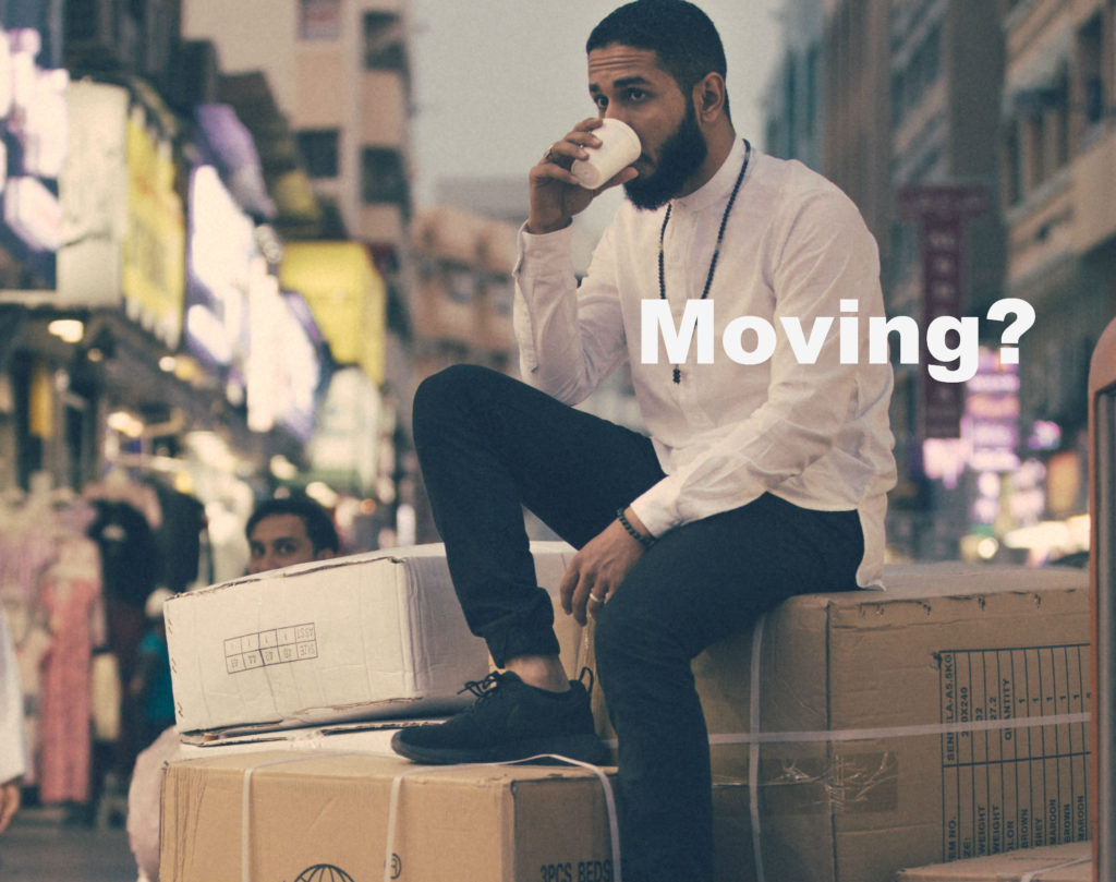 Man sitting on moving boxes drinking coffee. Moving? is written in white beside man.
